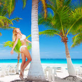 Woman on paradise beach. Pretty female next to palm tree, sexy girl wearing bikini, luxury tropical resort, enjoying warm sunny day, woman on paradise beach Royalty Free Stock Images