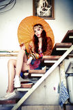 Woman with parasol. Beautiful woman in oriental clothes with parasol sit on stairs, indoor shot Stock Photography