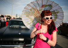 Woman with parasol in 1950's style. A woman dressed as Rockabilly, the hip culture of the 1950s style, and holding a decorative parasol. She stands among old Royalty Free Stock Photo