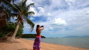 Woman in pareo taking picture of exotic beach with stock video footage