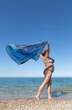 Woman with pareo walks along seashore Royalty Free Stock Images