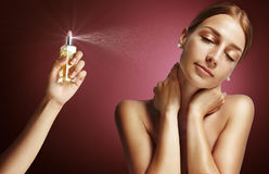 Woman and parfume. Woman hand spread parfume on an another woman stock image