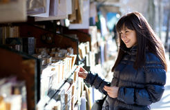 Woman in Paris selecting a book. Beautiful woman in Paris selecting a book in an outdoor bookseller box royalty free stock images