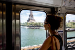 Woman in Paris subway train. Young woman looking on the Eiffel tower through the train window in Paris. Woman is out of focus Royalty Free Stock Photography