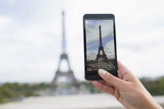 Woman in Paris taking pictures in front of Eiffel Tower, Cell ph. Female smart phone phtography travel France Stock Photography
