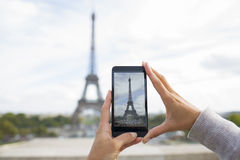 Woman in Paris taking pictures in front of Eiffel Tower, Cell ph. Female smart phone phtography travel France Stock Photo