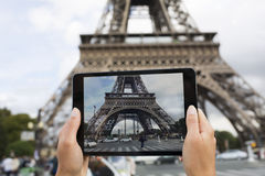 Woman in Paris taking pictures in front of Eiffel Tower with her Stock Image