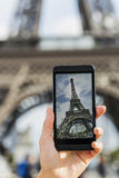 Woman in Paris taking pictures in front of Eiffel Tower with her. Female smart phone phtography travel France Stock Photography