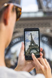 Woman in Paris taking pictures in front of Eiffel Tower with her. Female smart phone phtography travel France Royalty Free Stock Images