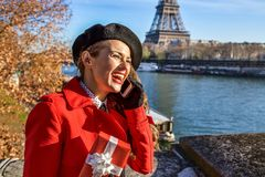 Woman in Paris using a cell phone and holding present box Stock Images
