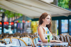 Woman in Parisian cafe with cocktail on a summer day Stock Image