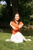 Woman in park. A young woman sits cross-legged and crossing her arms in a park Stock Images