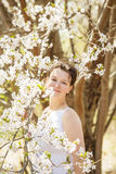 Woman in park among blooming trees in spring Royalty Free Stock Photos