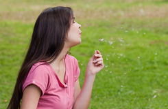 Woman in a park while blowing a dandelion Royalty Free Stock Photo