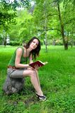 Woman in a park with book Stock Photos