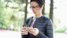 A woman in the park. Woman with coffee writing on smartphone stock video footage