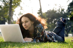 Woman in a park on computer Stock Photos