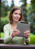Woman in Park with Digital Tablet Stock Image