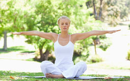 Woman in the park doing her yoga exercises Stock Photos