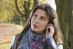 Woman in park with earphones Stock Images