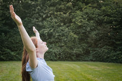 Woman in a Park - Freedom or Worship. Portrait of a free and happy young woman expressing her joy at an outdoor park Stock Images