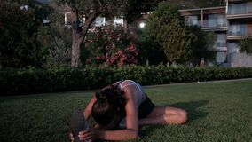 Woman in a park on the grass stretches her legs during fitness. stock video footage