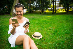 Woman in the park happy to use powerbank and continue listen music. While sitting in the parek Royalty Free Stock Photos