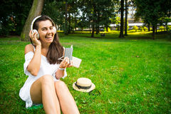 Woman in the park happy to use powerbank and continue listen music. While sitting in the parek Stock Photos