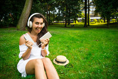 Woman in the park happy to use powerbank and continue listen music. While sitting in the parek Royalty Free Stock Images