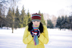 Woman in park Holding Mug. Girl in a yellow jacket in the winter in the park drinking from red cups Stock Photo