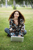 Woman in park with laptop Stock Photography
