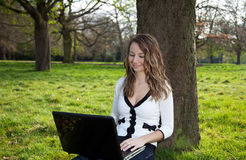 Woman in park with laptop Royalty Free Stock Images