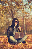 Woman in park with laptop Stock Images