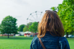 Woman in park looking at fun fair Stock Photography