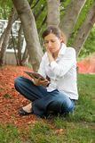 Woman in park with mobile tablet Royalty Free Stock Photos