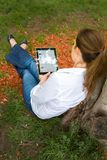 Woman in park with mobile tablet Stock Images