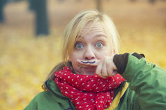 Woman in park with mustache painted on finger Stock Photography