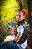 Woman in park outdoor with tablet and book. Woman in park outdoor with tablet and paper book deciding what to use Royalty Free Stock Photo