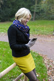 Woman in park with a phone Royalty Free Stock Image