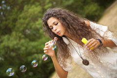 Woman in the park playing in bubbles cup Stock Images