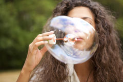 Woman in the park playing in bubbles cup Royalty Free Stock Photos