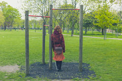 Woman in park by pull up bars Stock Photos