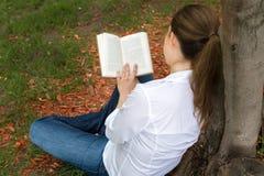 Woman in park reading a book Stock Photos