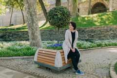 Woman in a park with a stone wall Stock Image