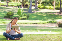 Woman in the park with a tablet computer Stock Image