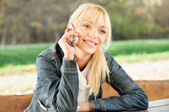 Woman at park taking a phone call. Blond woman at park taking a phone call Stock Image