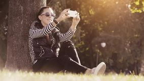 Woman in a park taking a photo on cellphone stock video footage