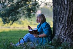 Woman in park with book on grass royalty free stock image