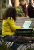 Woman in Park Using Computer. Woman in Park using a Laptop Computer.  It is an unusally warm winter day.  She is wearing a colorful coat and using a wireless Stock Photography