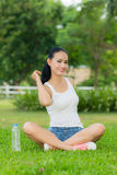 A woman in a park  with  water bottle. A woman in a park in the lotus position ,A woman in a park  with  water bottle Royalty Free Stock Image